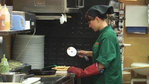 Kokki leikkaa pizzaa.