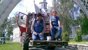 Talkoolaiset ajavat traktorilla juhlaportin alta.