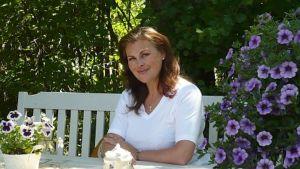 Anne Pohtamo-Hietanen kesäpaikkansa pihapöydän ääressä