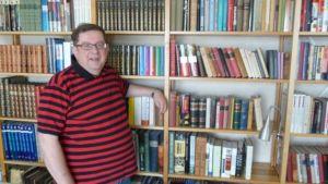 Selkokirjailija Pertti Rajala kirjahyllyn edessä.