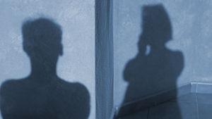 Miehen ja naisen varjokuvat piirtyvät seinään