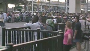 Ihmiset seisovat lentokentän ulkopuolella