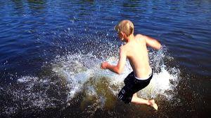 lapsi hyppää veteen