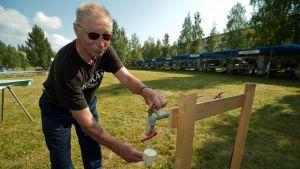 Rakennustalkoolainen Jorma Haaga herättäjäjuhlien vesipisteellä. Haaga on mukana talkoissa 11. kertaa.