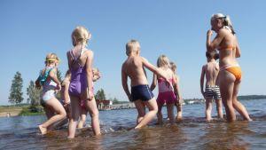 Lapset leikkivät rantavedessä.