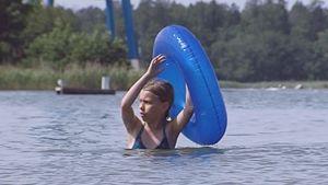 Tyttö uimassa uimarenkaan kanssa