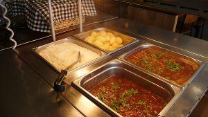 Kuvassa lihakastiketta, perunaa ja riisiä lounasravintolan tarjoilupöydässä