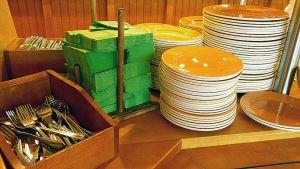 Kuvassa lounasravintolan noutopöytä ja aterimia, lautasia ja lautasliinoja