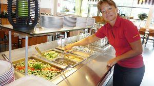 Kuvassa Reea Hotakainen hämmentämässä salaattia ravintolan lounaspöydässä