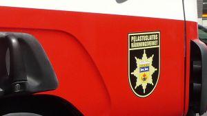 Kuvassa pelastuslaitoksen merkki paloauton kyljessä.
