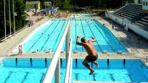 Poika hyppää yli seitsemän metrin korkeudesta altaaseen.