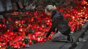 Vaaleatukkainen, nuorisovaatteisiin pukeutunut nainen on polvillaan ja lisää oman kynttilänsä punaiseen kynttilämereen.