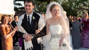 Marc Mezvinsky  vasemmalla, Chelsea Clinton oikealla. Chelsea hymyilee vieraille valkoinen morsiuskimppu vasemmassa kädessään.