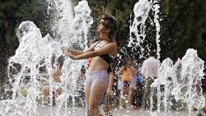 Tyttö vilvoittelee suihkulähteissä
