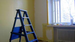 Remonttitikkaat puoliksi maalatussa huoneessa