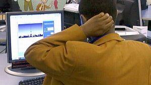 Maahanmuuttaja tietokoneen ääressä.