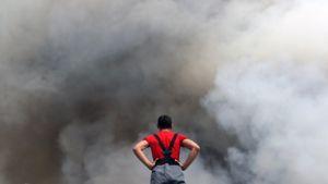 Punapaitainen palomies katselee selkä kameraan päin, kädet lanteillaan, edessään nousevaa savumuuria.