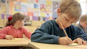 Ala-asteikäinen, ekaluokkalainen poika kirjoittaa luokkahuoneessa, oppilaita taustalla.