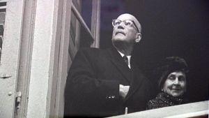 Valokuvaaja Caj Bremerin kuva Urho Kekkosesta ikkunassa. Kekkosen oikea käsi sydämellä takin liepeen alla. Kuva näyttelystä.