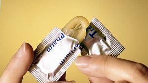 Henkilö avaa kondomipakkausta