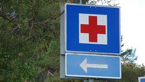 Terveysaseman opaste punainen risti valkoisella pohjalla.