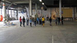 Koululaisia tutustumassa taidenäyttelyyn tehdashallissa