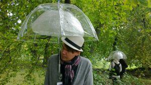 Mies tutkii rakkausrunoja sateenvarjon alla Töölönlahdella.