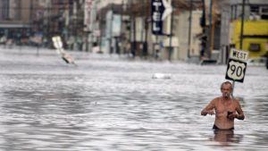 Mies kahlaa tulvivalla kadulla vyötäröään myöten New Orleansissa 30.8.2005.