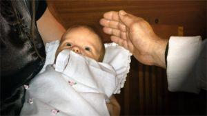 Vauvaa kastetaan.