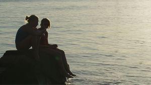 Kaksi tyttöä istuu kivellä vedenäärellä auringonlaskussa.