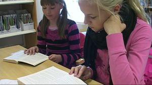 Julianna Stolt ja Iida Kvist lukevat kirjastossa.
