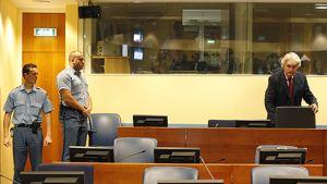 Vartijoita ja Bosnian entinen serbijohtaja Radovan Karadzic oikeussalissa.