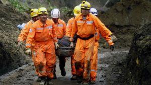 Pelastustyöntekijät kantavat ruuumispaareja Guatemalassa.
