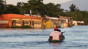 Ihmiset melovat veneellä tulvivalla kadulla.