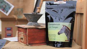 Kuvassa kahvimylly ja paketti tummapaahtoista kahvia.