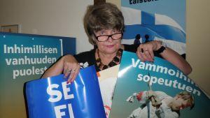Sotainvalidien Veljesliiton Pohjois-Karjalan piirin toiminnanjohtaja Tuulikki Leinonen esittelee syyskeräyksen julisteita vuosien varrelta.