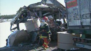 Palomies kävelee rekan perävaunun ja romuttuneen linja-auton välissä