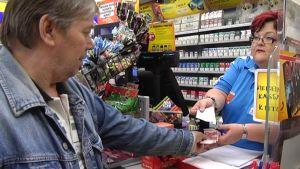 Mies maksaa käteisellä kioskiostoksensa.