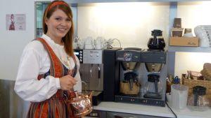 Kuvassa Paula-tyttö kahvinkeittimen ääressä kuparipannu kädessään