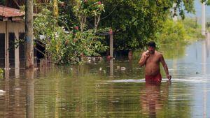 Mies kahlaa kadulla lähes vyötärölle ulottuvassa vedessä .