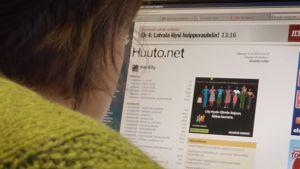 Nainen tutkii Huuto.net-sivustoa.