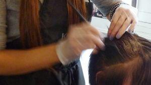 Kuvassa asiakas saa väriä hiuksiinsa kampaamossa