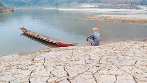 Thaimaalainen mies istuu pahoin kuivuneen Mekong-joen rannalla.