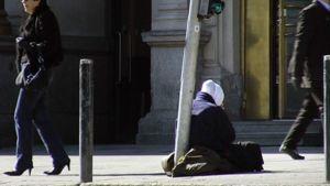 Nainen kerjää kadulla Helsingissä.