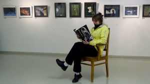"""Kuvassa  Kannuksen kamerakerhon puheenjohtaja Anja Jussila lukee """"Hetki""""-näyttelyn katalogia."""