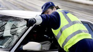 Poliisi osoittaa autoilijalle sormella