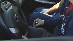 Nuori mies istuu kujettajan paikalla autossa kätensä vaihdekepillä.