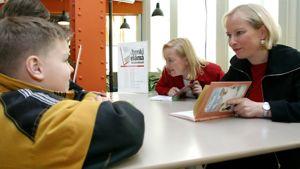 """Kirjailijat Tiina Nopola ja Sinikka Nopola kirjoittamassa lapsille omistuskirjoituksia """"Heinähattu ja Vilttitossu"""" -lastenkirjoihinsa."""
