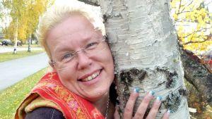 Kuvassa Onnellisuustohtori Sofia Kauko-Valli halaamassa puuta.