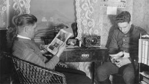 Kaksi miestä lehtiä lukemassa ja radiota kuuntelemassa.